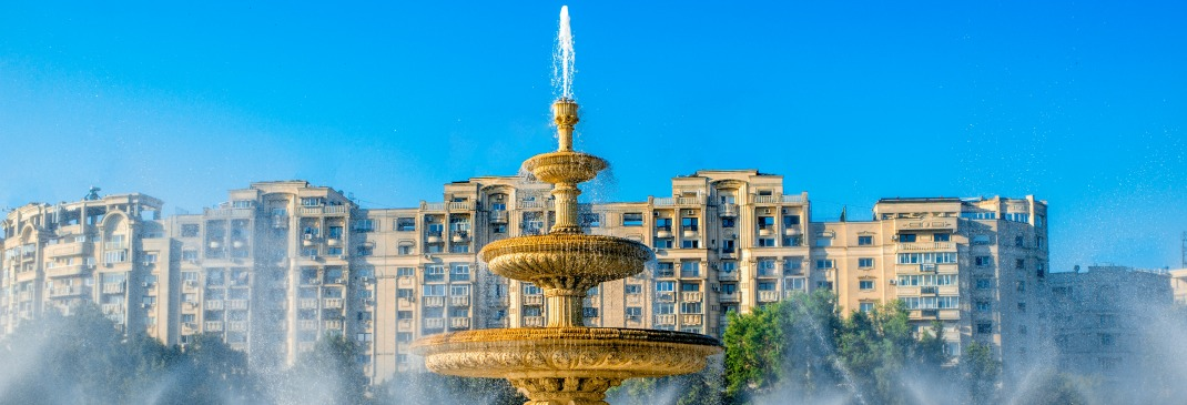 Water sprays out of the large gold fountain in the heart of Bucharest