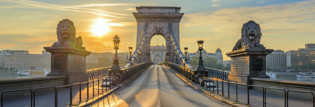 Budapest's Chain Bridge as the sun sets in the background