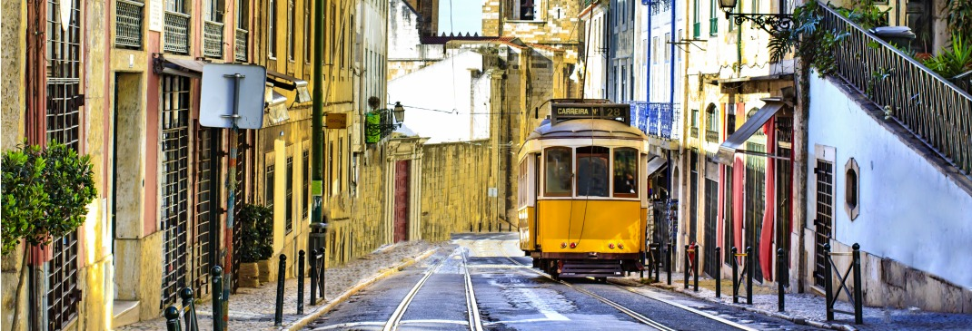 Typical yellow tram travelling down a street in Lisbon