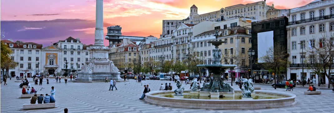 Rossio Square in Lisbon, Portugal filled with people as the sun starts to set