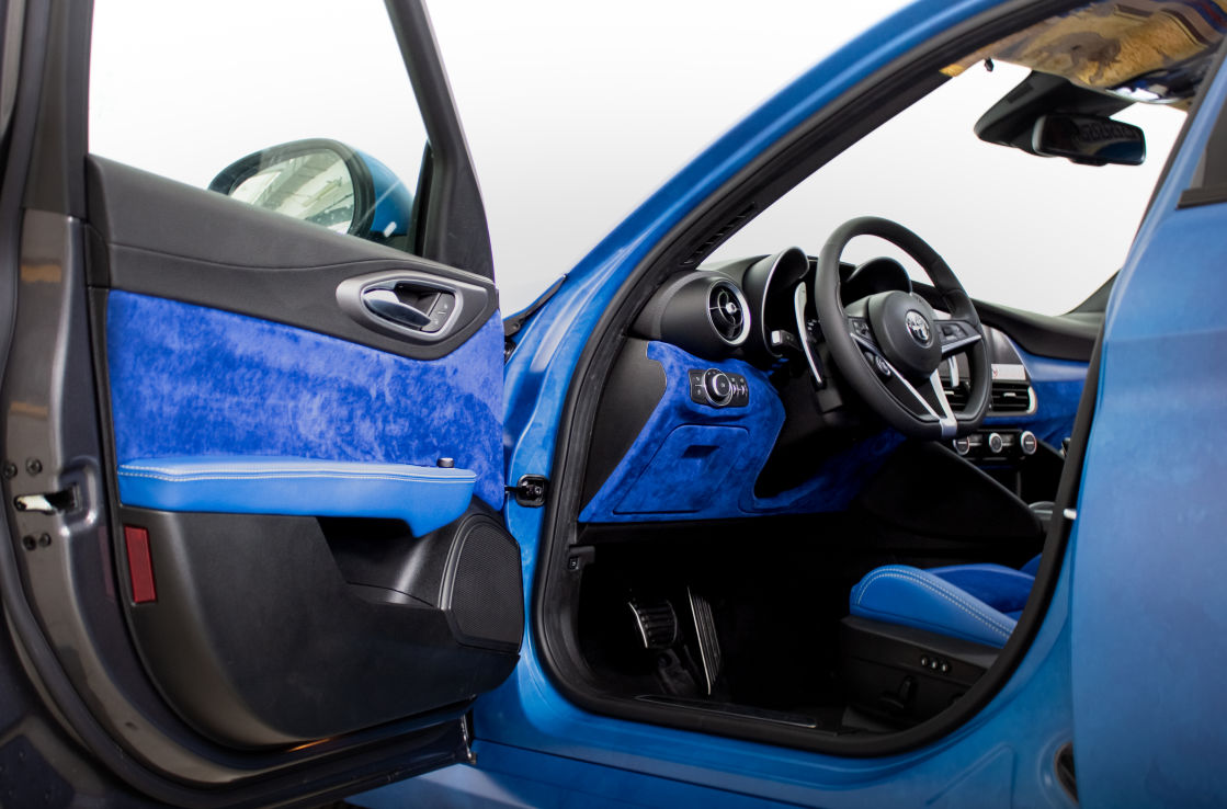 Interior shot of a blue Alfa Romeo Giulia, looking in through an open door