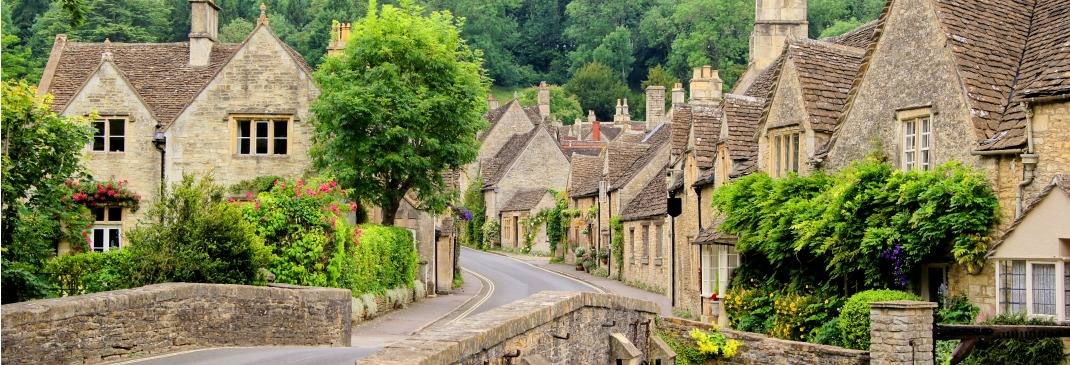 A road bridge winds its way through a picturesque village in the Cotswolds in England.